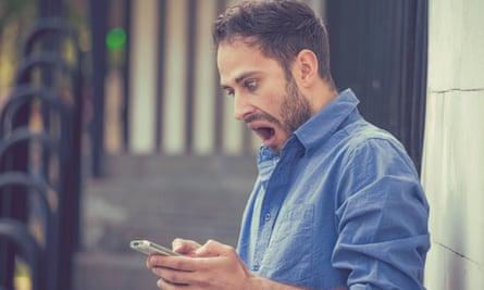 Anxious young man looking at phone
