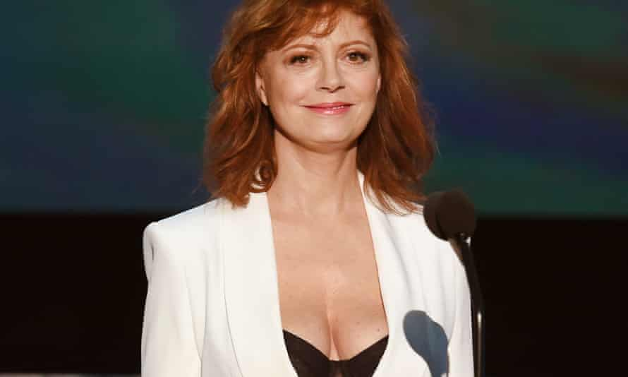 Susan Sarandon in white jacket and black bra.