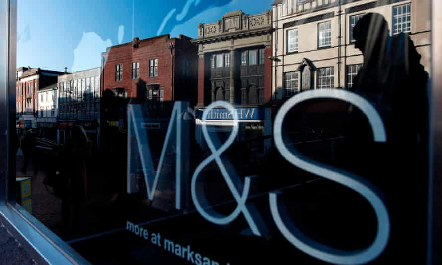 Shoppers are reflected in the window of a closed Marks and Spencer store