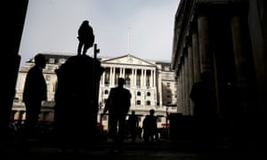 Pedestrians are silhouetted as the winter sun shines on to front of the Bank of England