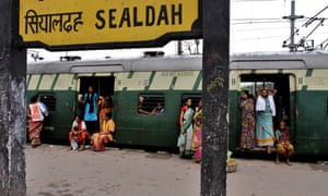 Stranded passengers wait on a platform for train services to resume following a power outage in Kolkata
