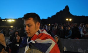 An Australian draped in the national flag pays his respects to the soldiers who died at Gallipoli, during the Dawn Service at the Anzac Commemorative Site in Gallipoli, Turkey, Wednesday, April 25, 2012.