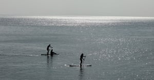 Paddleboarders enjoy calm sea conditions in Lyme Regis, England