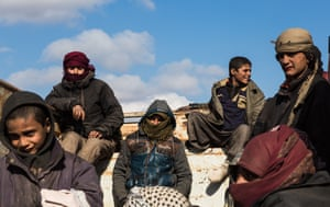 Young men and boys who fled heavy fighting in the city of Baghuz, wait in the back of a truck to be transported to the al-Hol refugee camp which houses suspected Isis families, 11 February 2019.