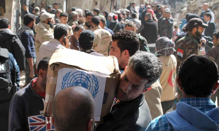 Residents of Syria's Yarmuk refugee camp, south of Damascus, receive food parcels from the UN Relief and Works Agency.