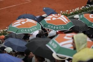 Spectators shelter from the rain.