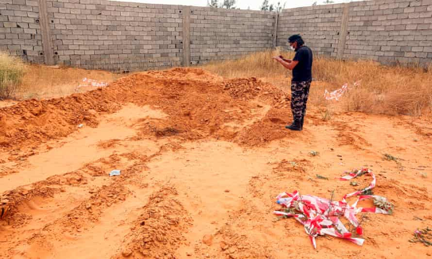 A member of security forces affiliated with the Libyan government of national accord stands at the reported site of a mass grave in the town of Tarhuna.