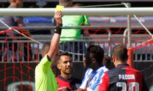 Pescara's Sulley Muntari is booked by referee Daniele Minelli