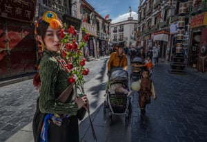 A woman has her photo taken wearing tradtional clothing as a Tibetan Buddhist woman and her family walk the kora near the Jokhang Temple, a UNESCO heritage site