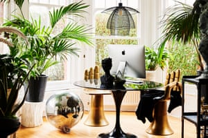 'The shiny surfaces bounce the light around': hand chairs, plants and mirror balls in the living room.