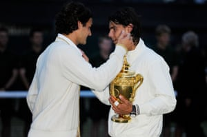 Federer embraces Nadal as the Spaniar clutches the trophy.