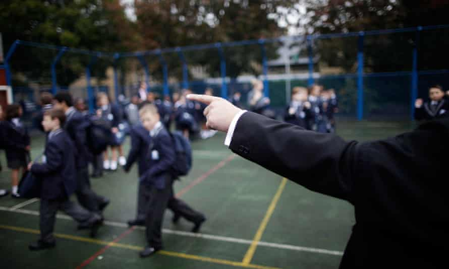 children in school playground, with an adult's long arm pointing at one of them
