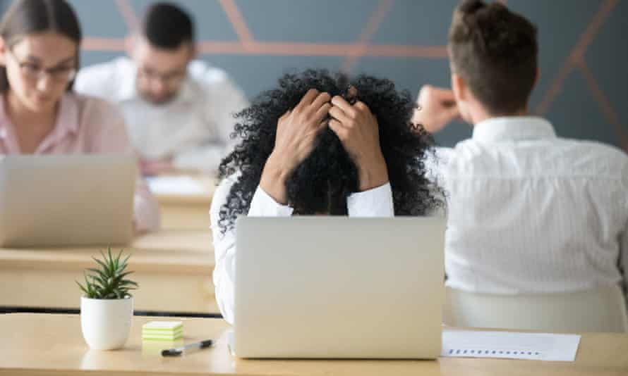 Frustrated woman at her laptop feeling despair in a shared office