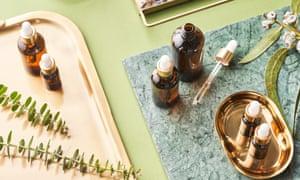 Au-dessus de bouteilles d'huiles essentielles et de brindilles de plantes placées sur un plateau en métal et une planche de marbre pendant l'aromathérapie et une séance de spa sur fond vert
