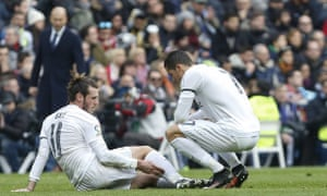 Gareth Bale chats to his Real Madrid team-mate Cristiano Ronaldo while lying injured in the match against Sporting Gijon