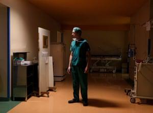 Man in green theatre scrubs stands alone in a corridor