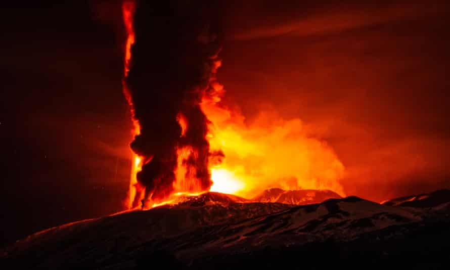 Fire and ash emissions spew from Mount Etna's Voragine crater.