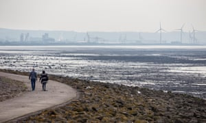 A couple walk along a footpath beside Bristol Channel near Avonmouth, one of Bristol's most impoverished areas.