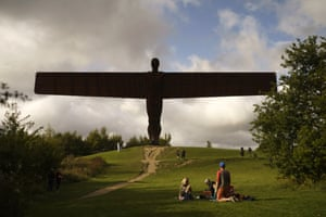 A family enjoy a picnic next to the Angel of the North in Gateshead, UK