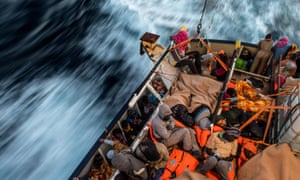 Asylum seekers sleep on the deck of a Spanish vessel after being rescued off the Libyan coast.