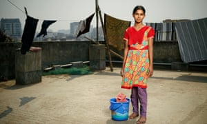 Girl stands on rooftop with washing