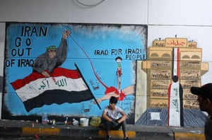 A protester rests in front of a political mural. It's entitled 'The new generation'