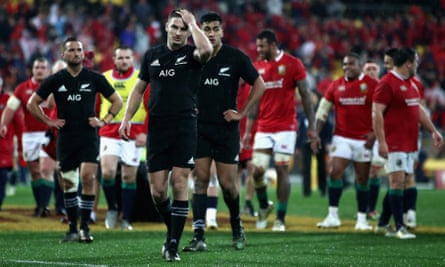 Beauden Barrett and his All Blacks team-mates show the pain of defeat as they leave the pitch and the Lions celebrate behind them in Wellington.