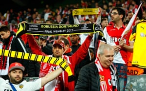 Monaco supporters with Borussia scarves react in a show of solidarity for their hosts after the match was postponed.