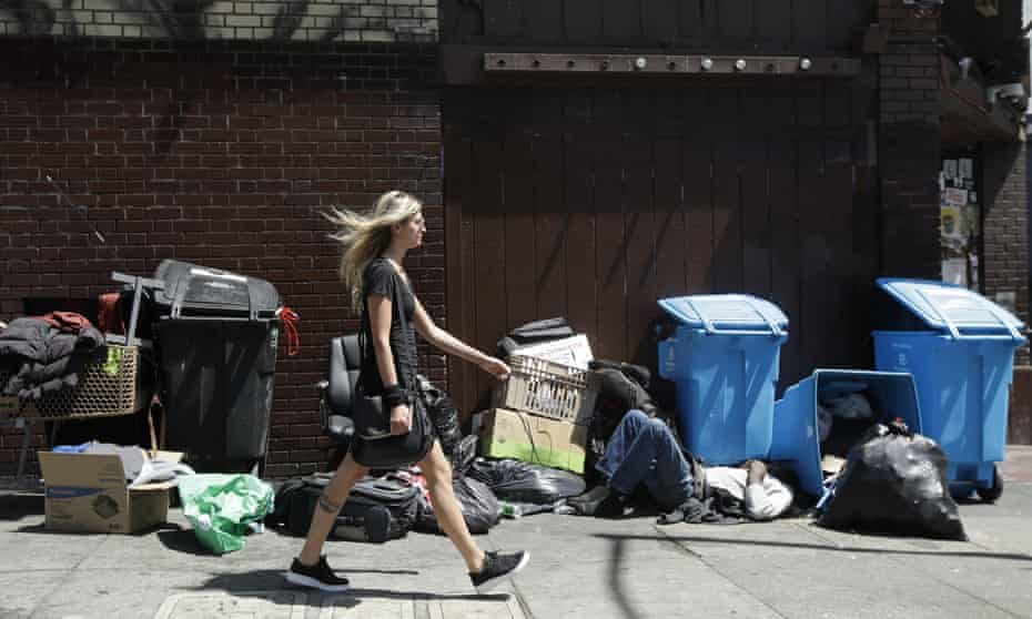 A homeless man sleeping on the street in San Francisco, not far from the city's 'gleaming corporate palaces'