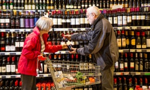 shoppers discuss which wine to buy in a supermarket