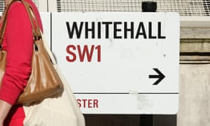 Pedestrian walking past a road sign for Whitehall