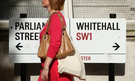 A woman walks past signs in Westminster, London
