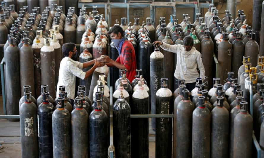 People carry oxygen cylinders after refilling them in a factory in Ahmedabad. India recorded 352,000 Covid cases on Monday.