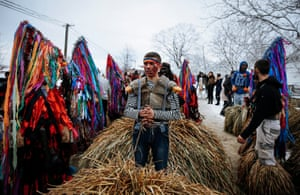 Young men prepare to put on huge costumes made out of hay and reeds