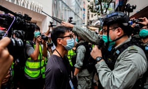 Police guard an MTR station exit near the legislative council in Hong Kong on 27 May ahead of a debate over a law that bans insulting China's national anthem.