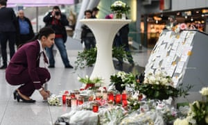 A Germanwings employee places flowers in commemoration of the victims of the Germanwings plane crash in the French Alps, at the airport in Duesseldorf