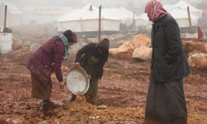 Displaced Syrians clear an area to set up tents after fleeing violence in Maarat al-Numan earlier this month.
