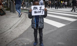 A boy holds a sign during a protest in downtown Los Angeles, Friday, May 29, 2020, over the death of George Floyd, who died in police custody on Memorial Day in Minneapolis. (AP Photo/Christian Monterrosa)