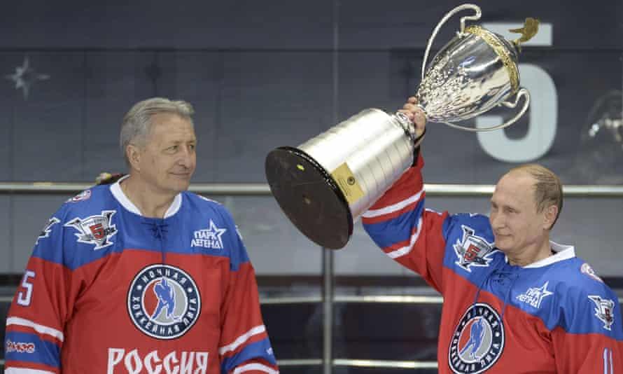 Vladimir Putin lifts a trophy