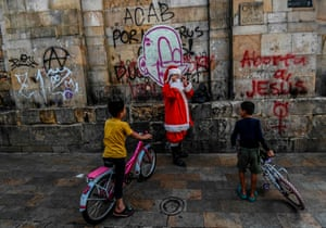 Venezuelan migrant boys look at a man dressed as Santa Claus in Bogotá, Colombia