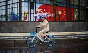 Aw oman rides a shared bicycle past an image of the Chinese flag in Wuhan.
