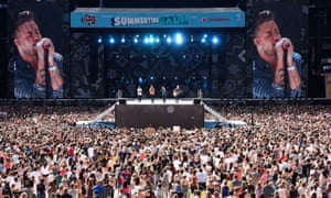 One Direction perform in daytime at the 2015 Capital FM Summertime Ball at Wembley Stadium in London, with a backdrop of giant TV screens