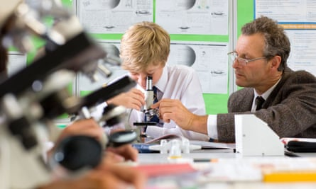 Student and teacher with microscope in science class