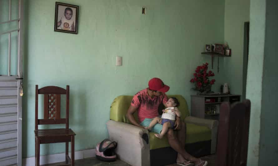 Dejailson Arruda holds his daughter Luiza, who was born with microcephaly when her mother was infected with the Zika virus, at their home in Santa Cruz do Capibaribe.