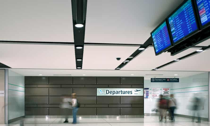 Blurred people walk through an airport departure lounge