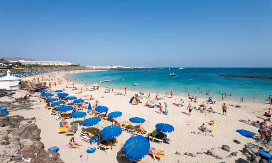 The main beach, Playa Blanca, in Lanzarote, filled with holidaymakers on the sand and under beach umbrellas. Canary Islands, Spain.