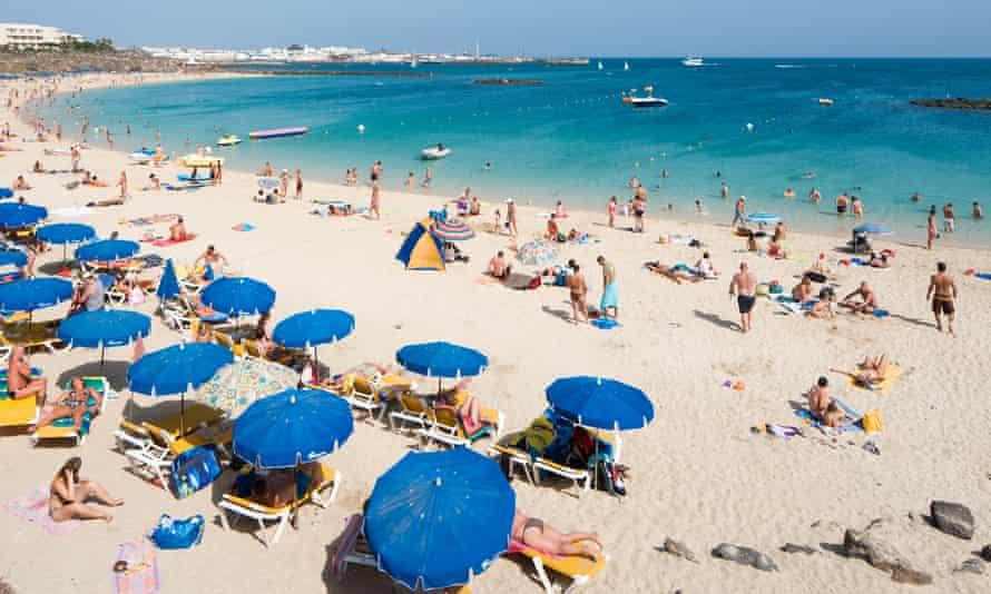 a busy, sandy beach on a bright, sunny day