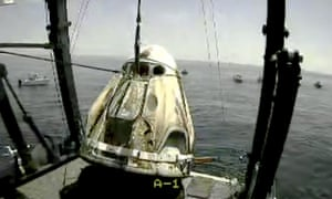 The SpaceX capsule is lifted onto a ship