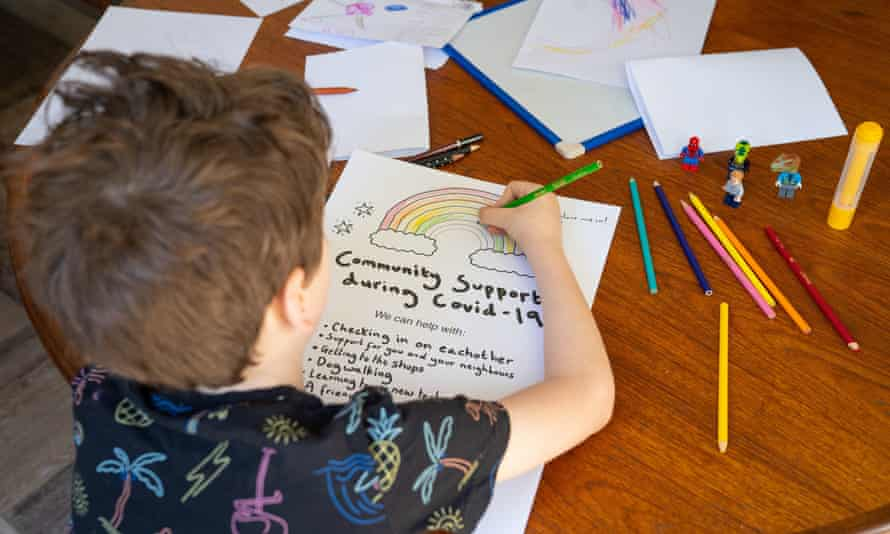 A boy colours a rainbow poster