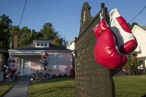 A pair of boxing gloves hang from the sign in front of Muhammad Ali's childhood home on Grand Avenue